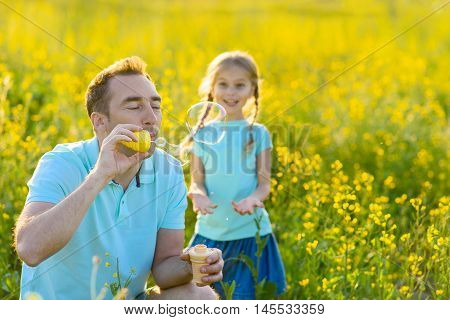 Bubbles of fun. Happy father having fun with his daughter and blowing soap bubbles outdoors, crouching