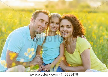 Family time in great outdoors. Cute happy family spending time out in nature together and looking at camera, smiling