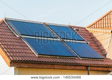 Vacuum collectors- solar water heating system on red roof