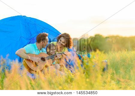 Enjoying camping trip. Smiling little girl sitting near tent with her family on camping while father playing guitar