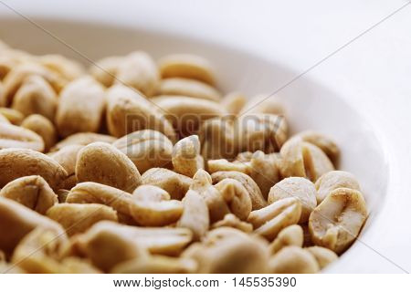 Fried salted nuts peanuts on a white background in a plate. Assorted snack pile of nuts. Abstract background salted nuts. Roasted salted peanuts in bowl, side view. Halves of roasted peanuts.