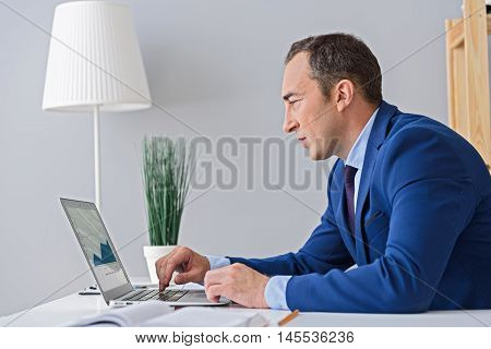 Working on his latest project. Photo of adult businessman working with digital tablet, carefully studying graph on screen