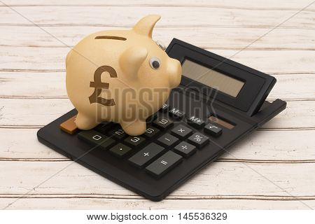 The Pound Currency A golden piggy bank and calculator on a wood background with symbol of the Pound