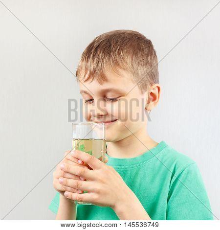Little blonde boy with a glass of fresh lemonade