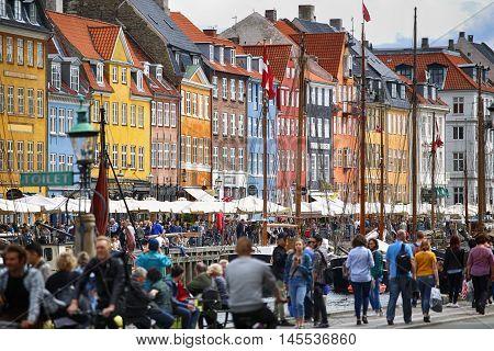 Copenhagen Denmark - August 14 2016: Boats in the docks Nyhavn people restaurants and colorful architecture. Nyhavn a 17th century harbour in Copenhagen Denmark