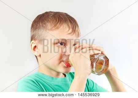 Beautiful blonde child drinking a fresh lemonade