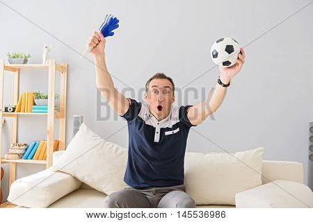 I am the most ardent fan. Shot of handsome adult man celebrating while watching sports match on tv at home, holding football attributes