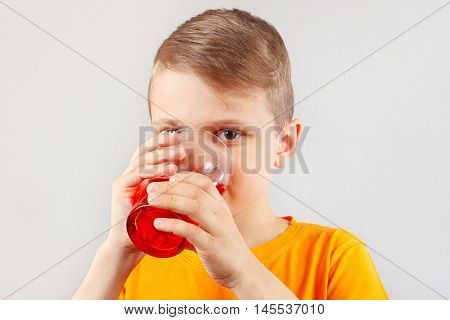 Little funny boy drinking a fresh red lemonade