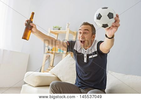This is our victory. Handsome man celebrating victory of his team, holding bottle of beer and ball in hands