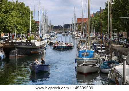 Copenhagen Denmark - August 15 2016: View on canal with tourist boat beetwen Overgaden Oven Vandet street and Overgaden Neden Vandet street from bridge Sankt Anne Gade in Copenhagen Denmark