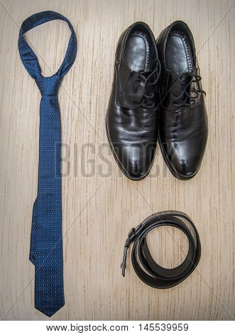 Set of men's clothing and shoes on wooden background. . Black elegant accessories pieces isolated on white wooden table.