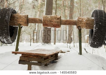 Lounger for push ups wooden homemade barbell from the chest at outdoor sportsground in snowy wood.