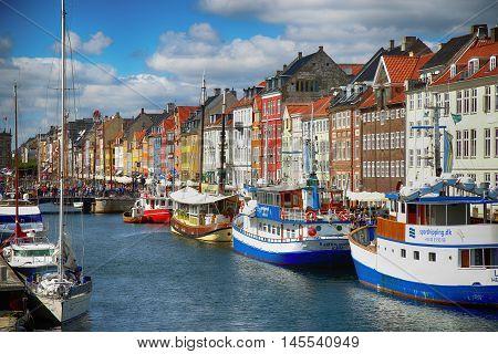 Copenhagen Denmark - August 15 2016: Boats in the docks Nyhavn people restaurants and colorful architecture. Nyhavn a 17th century harbour in Copenhagen Denmark