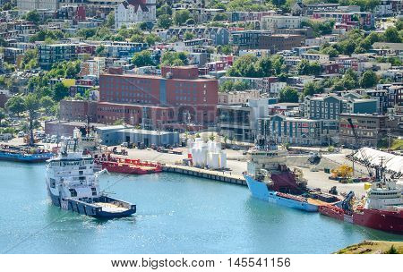 Commerce, trade, cargo and ships of all kinds lined up along St John's Harbour in Newfoundland Canada.  Boats slowly move about amongst those docked in harbour.