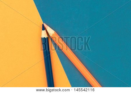 Orange And Dark Blue Coloured Pencils And Paper