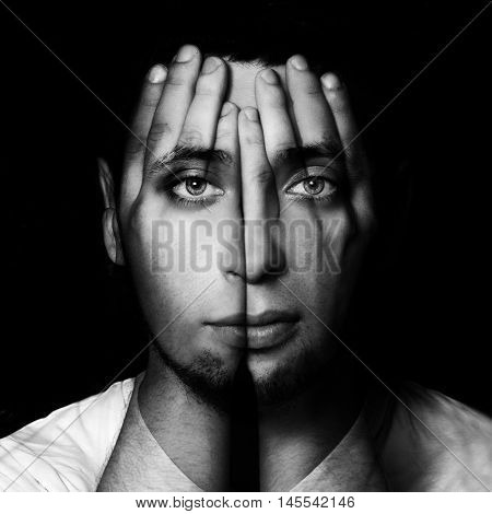 Surreal portrait of a man covering his face and eyes with his hands.Double exposure