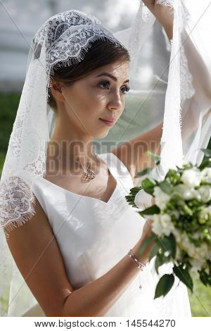 The beautiful bride with bouquet in park