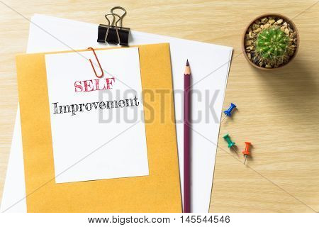 Self Improvement, message on the white paper / business concept / wood desk , copy space / business concept / view from above, top view