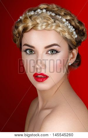 Beautiful young woman with full red lips and braid hairstyle. Beauty shot over red background.