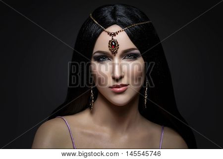 Beautiful young caucasian woman with long black hair and arabian style makeup. Vintage accessory on head. Studio shot over dark background. Copy space.