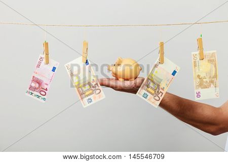 Male Hand With Banknote And Piggybank