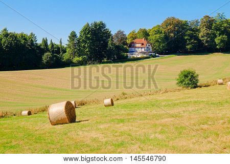 Rural landscape with coils of hay on the agricultural field and a lonely typical German house in a sunny day. Bad Pyrmont, 28.08.2016.