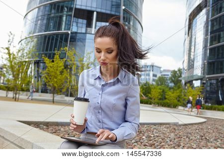 Woman enjoying coffee outside the office building