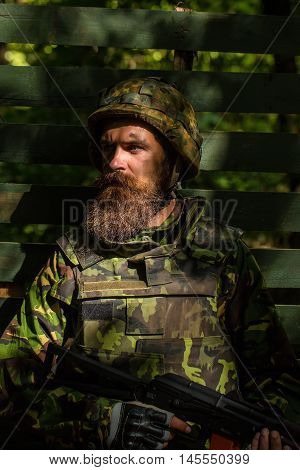 Young soldier with sad bearded face in military helmet and camouflage with gun on wooden background