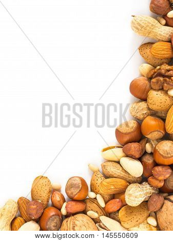 Background of mixed nuts - hazelnuts, almonds, walnuts, pistachios, peanuts, pine nuts peeled and not peeled - vertical with copy space. Isolated one edge. Top view or flat lay
