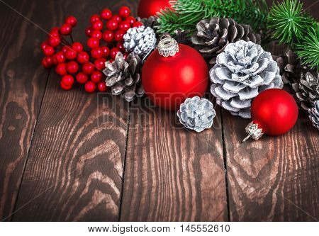 Christmas decoration with red balls pinecone and branch firtree on old wooden board holiday greeting card