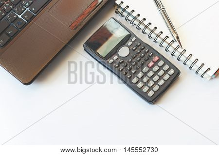 savings finances economy and office concept. Close up detail view of a white work desk with a laptop computer and a calculator with numbers on the screen Pen on notebook soft focus.