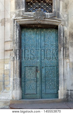 Old blue metal forged door in a stone building background