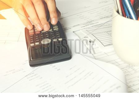savings finances economy and office concept. Business people counting on calculator sitting at the table. Close up of hands and stationery soft focus