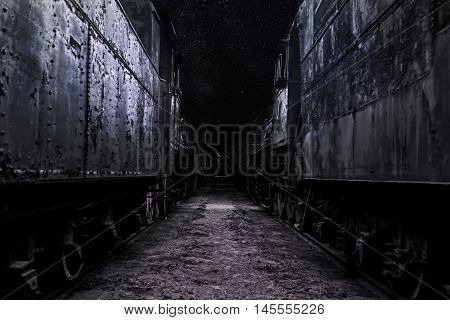 Cemetery of old steam locomotives at night.