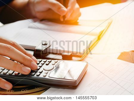 close up business man or lawyer accountant working on accounts using a calculator and writing on documents soft focus