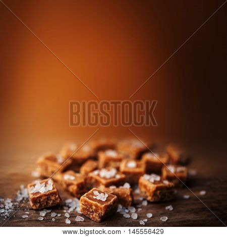 Salted caramel pieces and sea salt close up top view. Butterscotch toffee caramel with copyspace