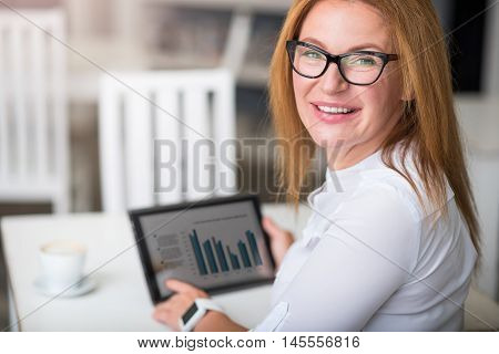 Full of positivity. Overjoyed senior woman sitting at the table and smiling while holding tablet