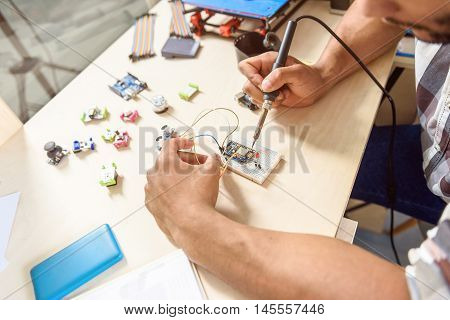 Professional male engineer is soldering 3d printing components with concentration. He is sitting at table in office