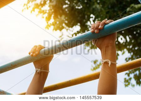 Little boy hanging bar by 2 hands the outdoor exercise equipment in public park soft focus