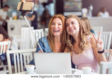 Selfie time. Cheerful joyful smiling mother and daughter sitting at the table and making photos wile resting in the cafe