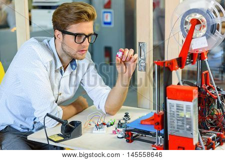 Skillful male engineer is analyzing components of 3d printer with seriousness