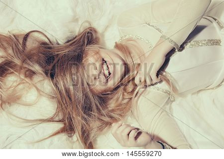 small girl kid with long blonde hair and pretty smiling happy face in prom dress lying on white fabric closeup