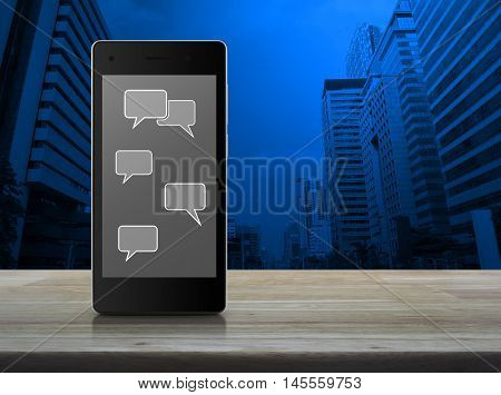 Social chat sign and speech bubbles on modern smart phone screen on wooden table in front of city tower background Social network concept