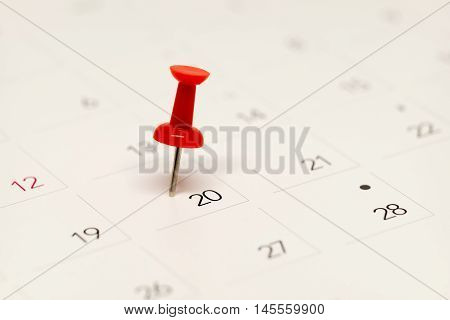 Red pushpin on calendar for important date.