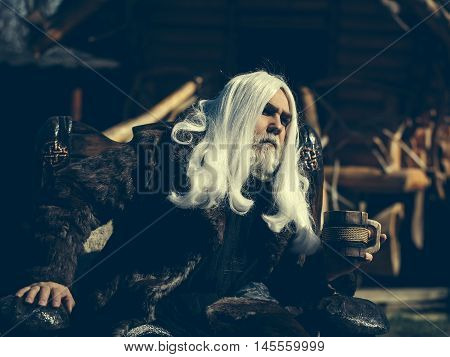 Druid old man with long silver hair beard in fur coat sits in chair with wooden mug on blurred background