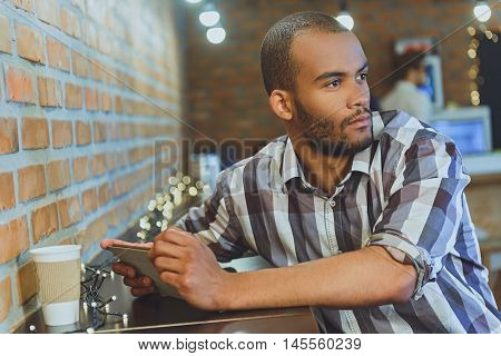 Young African man is waiting for someone in cafeteria. He is holding tablet and looking aside with anticipation