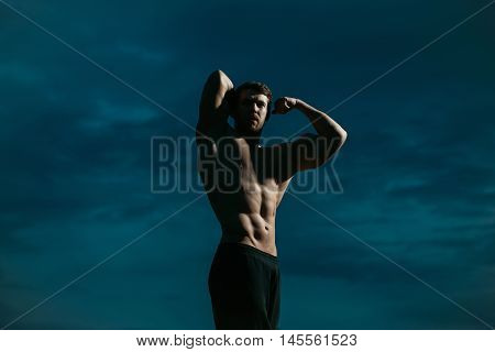young handsome athletic man with muscular fit body and sexy torso of macho guy bodybuilder training sport with raised hands outdoor on dark blue sky background