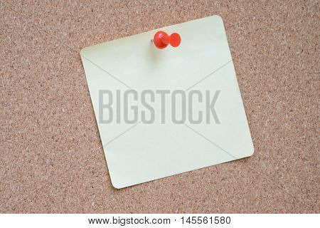 Yellow sticker pinned red pushpin with cork background.