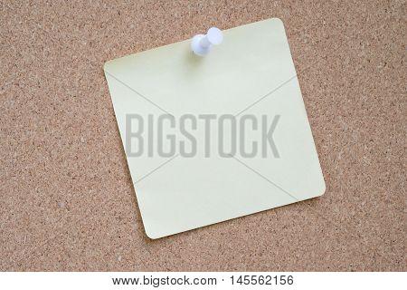 Yellow sticker pinned white pushpin with cork background.