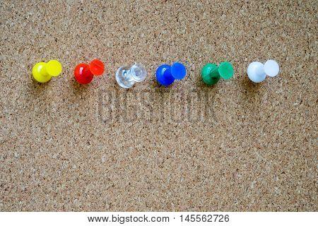 Closeup of colorful pushpin on cork board.